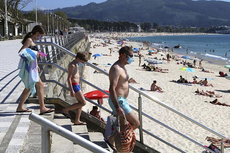 Trois vacanciers viennent avec un masque sur la plage de Samil à Vigo.