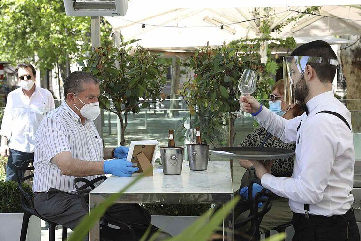 Un serveur sert un client sur la terrasse d'un bar à Madrid.