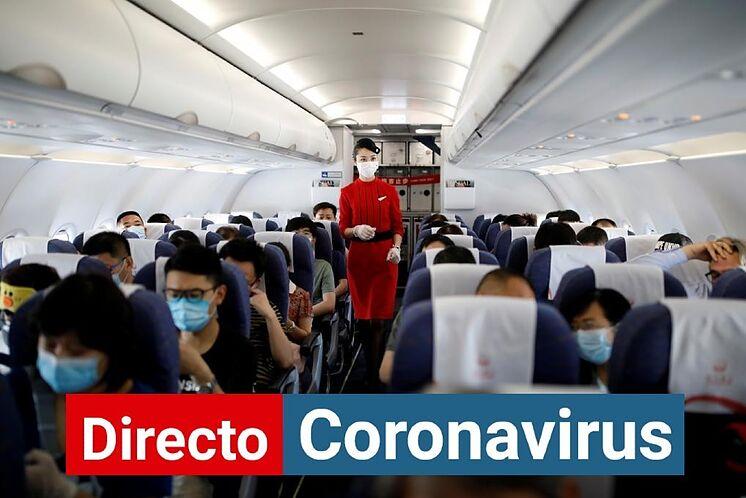 Un agent de bord marche dans un avion rempli de passagers dans un aéroport ...